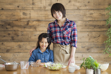 Cute little girl and her beautiful mom. They are smiling while cooking in kitchen at home.