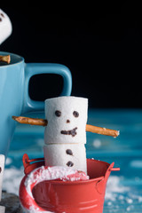 Snowmen from marshmallows. New year snowmen. A festive table of tea and sweet snowmen on a blue table.