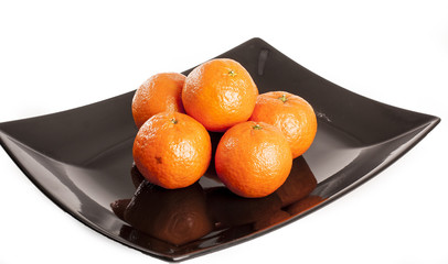 Mandarin orange. Pile of oranges mandarins on plack plate and isolated white studio background. Food photo.