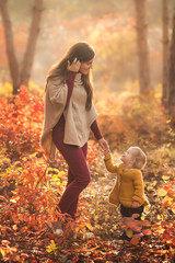 Happy family mother and child daughter playing in nature autumn park on sunset