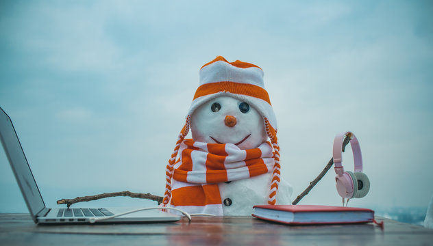 Snowman in winter with laptop, headset and book