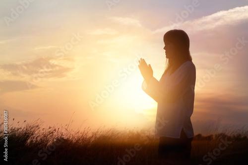 Leinwandbilder Woman praying and practicing yoga on nature sunset background, hope concept
