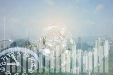 Double exposure of alarm clock and coin in glass jar with city background and graph, time for savings money concept.