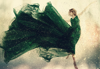 Beautiful woman in a green dress jumping