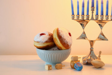 image of jewish holiday Hanukkah background with traditional spinnig top, menorah (traditional candelabra) and donut.