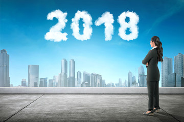 Back view asian business woman looking cloud with 2018 sign
