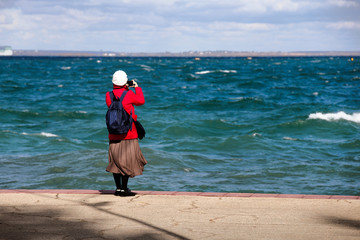 A middle-aged woman photographs the seascape. Embankment, strong wind, waves.