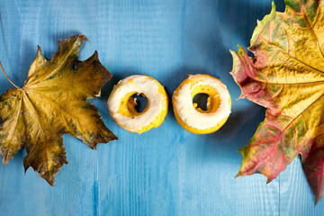 Two pumpkin donuts on a light blue wooden background with maple leaves. Looks like eyes on a face.