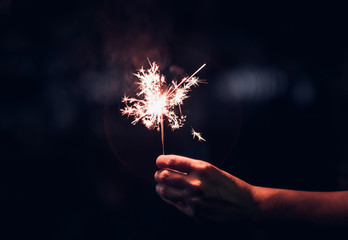 Hand holding burning Sparkler blast on a black background at night,holiday celebration event party,dark vintage tone.