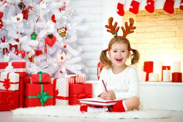 child girl writing letter santa home near Christmas tree.