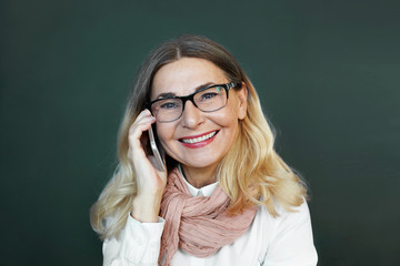 Studio shot of stylish senior female wearing rectangular eyeglasses and pink scarf over white shirt smiling happily, sharing good positive news with her friend, having nice phone conversation