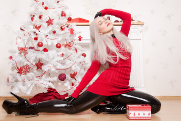 Beautiful Fashionable Blonde Woman Wearing Black Latex Rubber Catsuit, Fetish High Heels Boots and Red Lond Sweater Posing Near The White Christmas Tree and FirePlace With New Year Boxes Of Presents