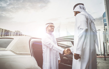 Two arabian businessmen talking about business in the company limousine
