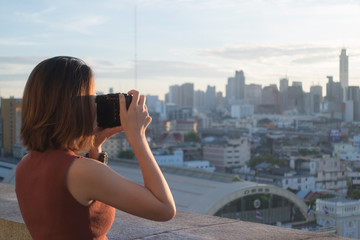 Young woman take photo of Bangkok view in morning. Photographer