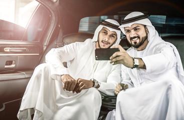 Two arabian men taking selfie inside their limousine
