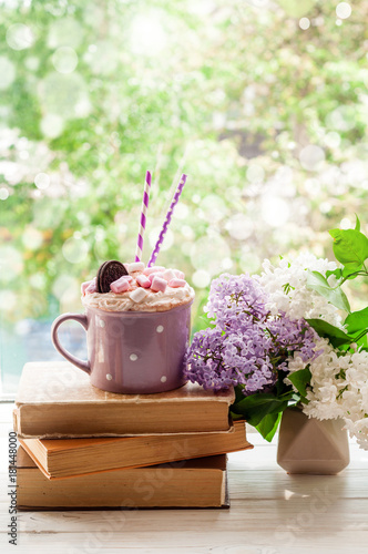 coffee cup with marshmallow open book and flowers bouquet on window
