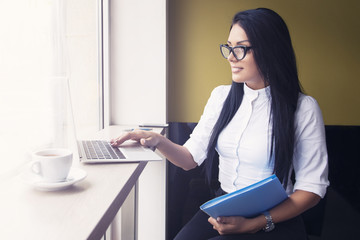 Business woman roking on laptop