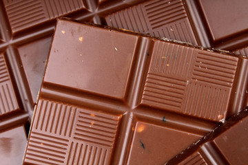 Chocolate bars as background. Milk and dark shiny chocolate texture. Stack chocolates pattern. Stunning beautiful cacao brown dessert sweets. Studio photo.