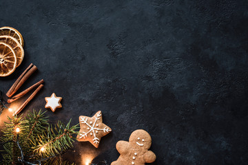 Christmas lights, Gingerbread cookies, Fir tree, Spices and Dried oranges on Dark Stone Background. Winter Holidays Frame Background or Wallpaper with Copy Space. Design mock up