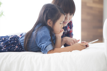 Mother and daughter are using a digital tablet at the table together.