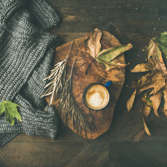 Autumn or Fall morning coffee concept. Flat-lay of knitted woolen grey sweater, wooden tray, mug of coffee and yellow fallen leaves over dark rustic wooden table background, top view, square crop