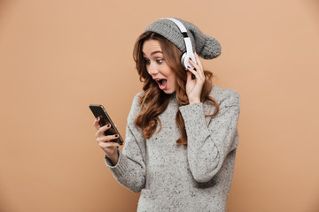 Portrait of amazed charming girl in winter clothes looking at mobile phone while listening to music