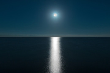 Seascape with the full moon over the sea and the moon glade