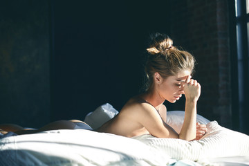 Tender sensual female wearing white thongs lying on sunlit bedclothes, feeling hard to get up, having serious look, copy space in background for your text, information on promotional content