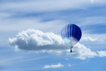 Hot air blue ballon against blue sky with white fluffy clouds and copyspace for text