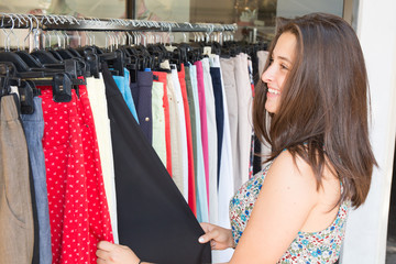 Smiling young woman looking at clothes hanging on the rail