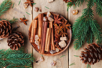 Mixed christmas spices in plate on wooden rustic table top view. Anise star, cinnamon sticks and brown sugar.