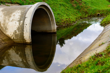 Concrete culvert pipe hole system draining sewage water. Environmental disaster