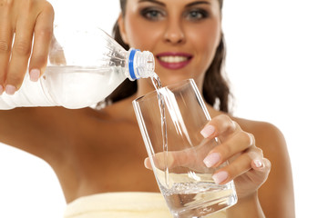 young woman pouring water from a plastic bottle in a glass
