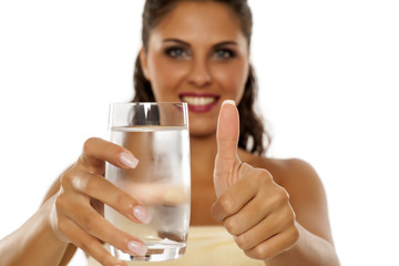 young woman holding a glass of cold mineral water and showing thumbs up