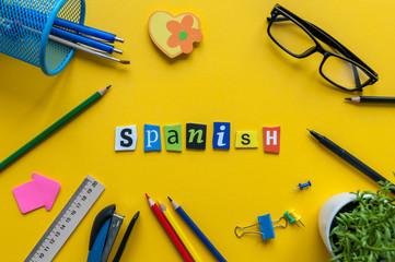 SPANISH made with carved letters on yellow desk with office or school supplies, stationery. Concept of Spanish language courses