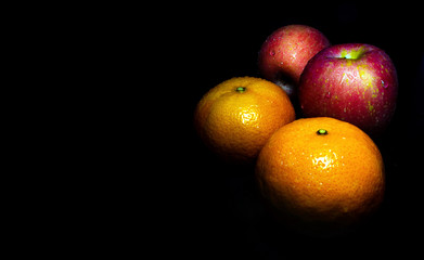 Water droplet on glossy surface of freshness orange and red apple