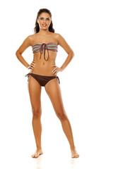 Young pretty brunette posing in bikini on white background