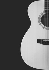 black and white acoustic guitar showing curve of body shape, isolated on black. music background
