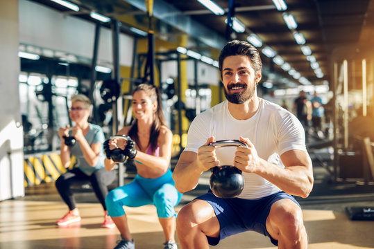Attractive handsome bearded man holding kettlebell and doing squats in a fitness group with two girls in the modern gym.