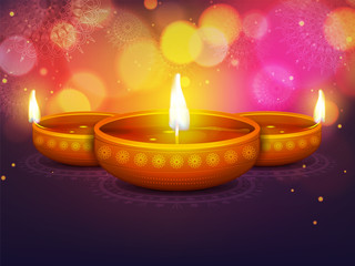 Illuminated oil lit lamps on floral design decorated background for Diwali(Indian festival of lights celebration).