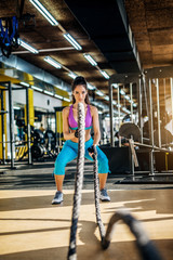 Attractive strong fitness woman doing battle rope exercise in the modern sunny gym.