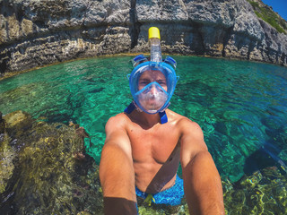 Selfie photo of a young healthy muscular man with a snorkelling mask standing in the turquoise exotic sea near the rocks for summer holidays.