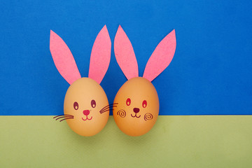 Easter eggs with rabbit ears and faces on paper background