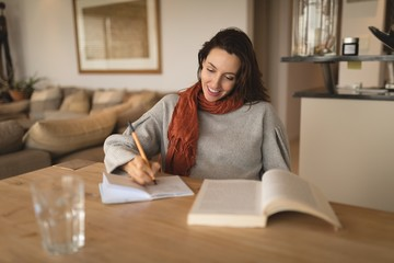 Pregnant woman writing in a book