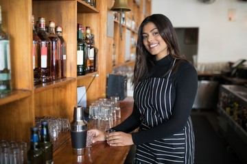 Smiling waitress standing at counter in bar