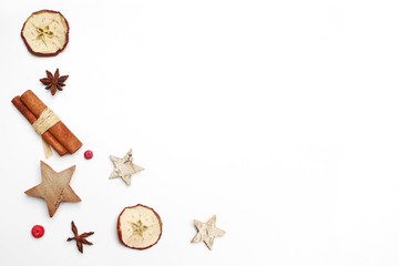 Christmas festive styled stock image composition. Decorative pattern. Cinnamon sticks, red berries, dried apple fruit, anise and wooden stars isolated on white wooden background. Flat lay, top view.
