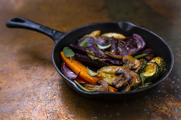 Baked vegetables with herbs in a cast iron pan.