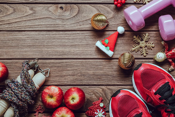 Fitness, healthy and active lifestyles love concept, dumbbells, sport shoes, skipping rope or jump rope and apples with Christmas decoration items on wood background.