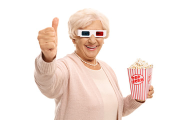 Mature woman with 3D glasses and popcorn making a thumb up gesture