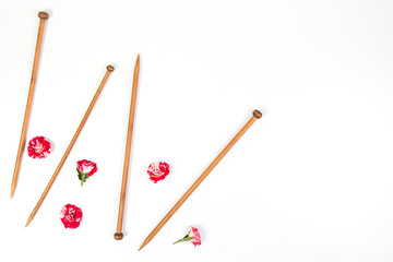 Wooden knitting needles and fresh roses on white background
